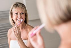 Woman Brushing her Dentures